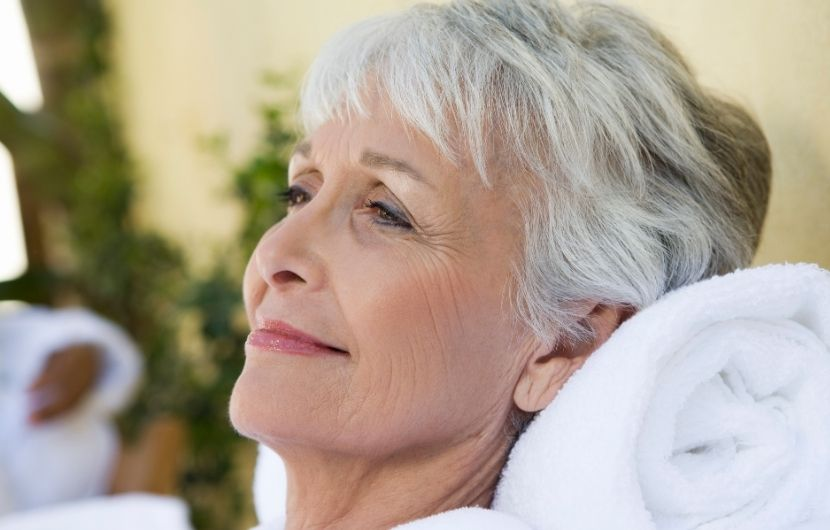 A senior woman enjoying her self-care time at a spa