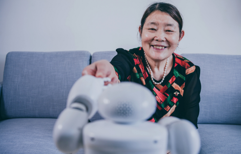 An elderly woman is smiling and shaking hands with a robot