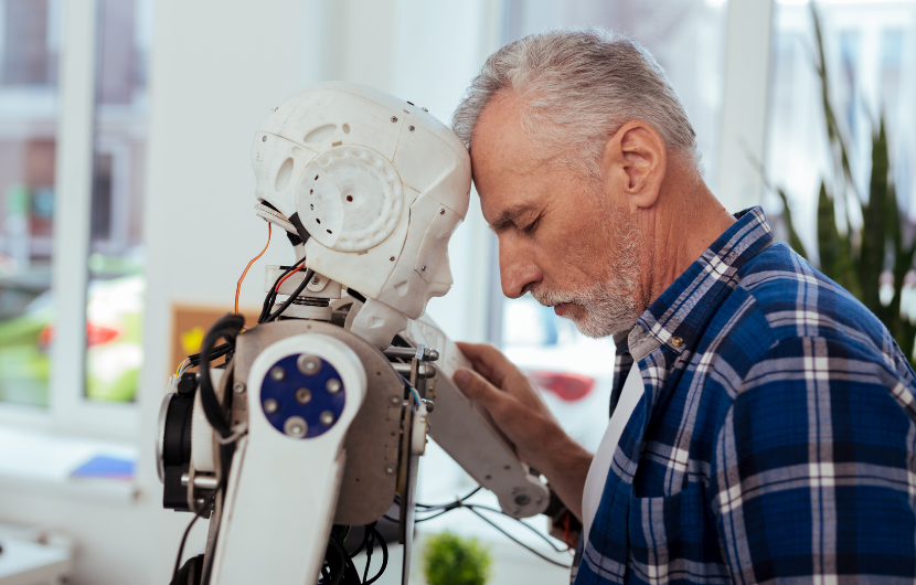An elderly man is leaning towards his personal robot